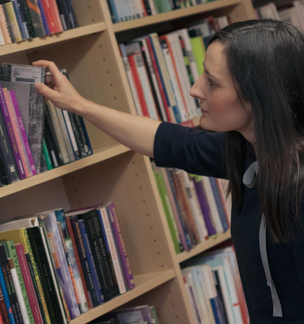 Knjižničarka uzima knjigu s police